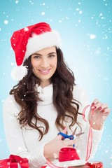 Composite image of smiling brunette in santa hat packing gifts