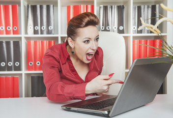 Angry screaming business woman working with computer