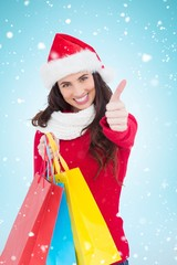 Composite image of festive brunette holding gifts and thumb up
