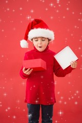 Composite image of festive little boy opening a gift