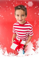 Composite image of festive little boy holding a gift