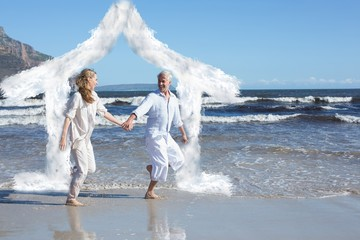 Composite image of happy couple skipping barefoot on the beach