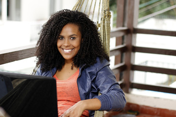 Beautiful black woman with laptop on hammock, and smile