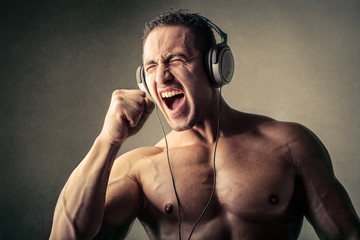 Muscular man listening to music