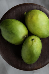 Tree ripe green mangoes on the wooden table