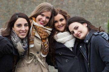 Portrait of four attractive young women, smiling and embracing