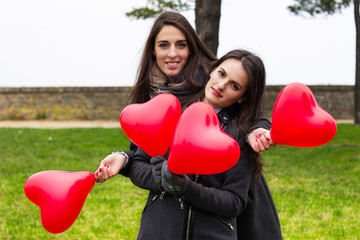Two smiling girls holding hearts