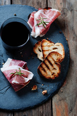 Traditional Italian crostini with ham and red wine