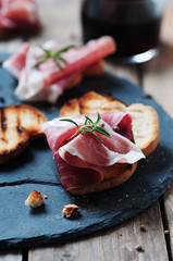 Traditional italian crostini with ham and wine