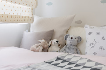 kid room with dolls and pillows on bed