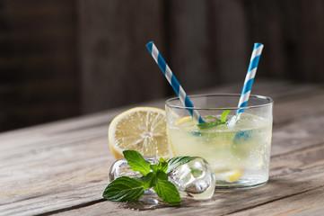 Lemonade with fresh lemon on wooden backgroun