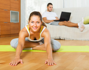 Girl practicing yoga and her boyfriend resting