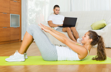 Girl practicing fitness and boyfriend resting on couch