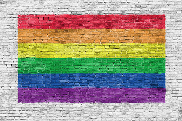 Rainbow flag painted over brick wall
