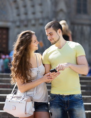 Happy couple using the map at smartphone