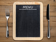 Fork, knife and blackboard menu on wooden background - 74498403
