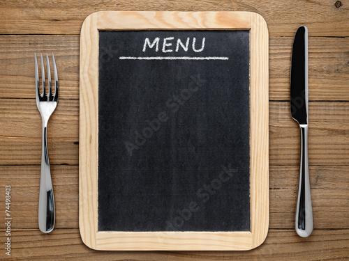 Leinwandbild Motiv Fork, knife and blackboard menu on wooden background