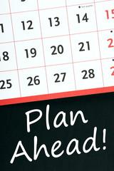 Plan Ahead! written on a blackboard next to a calendar