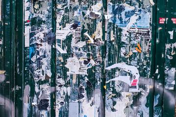 Vecchi poster pubblicitari strappati affissi su muro