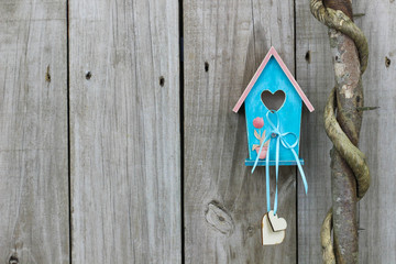 Blue birdhouse with hearts and flowers hanging on fence by tree