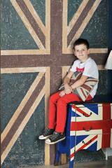 the boy sits on the nightstand on the English flag background
