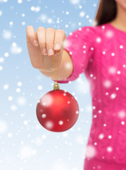 close up of woman in sweater with christmas ball