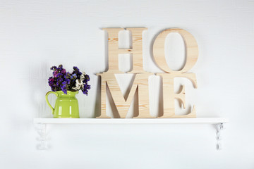 Home interior: stylish shelf with bouquet of wildflowers and