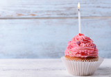 Fototapety Delicious birthday cupcake on table on wooden background