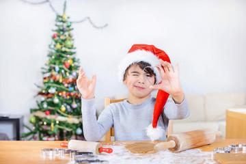 Cute boy is scuniting eye to look through a baking shape