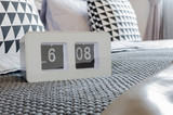 modern white alarm clock on bed