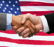 close up of handshake over american flag