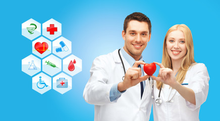 smiling doctors cardiologists with small red heart