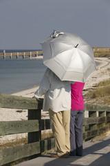 Holidaymaker holding UV protecting umbrella