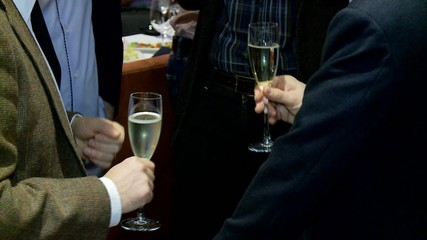 Hands of men with a glasses of of champagne.