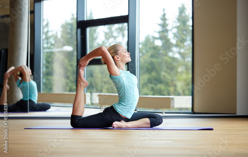 canvas print picture smiling woman stretching on mat in gym