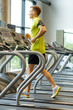 man with smartphone exercising on treadmill in gym