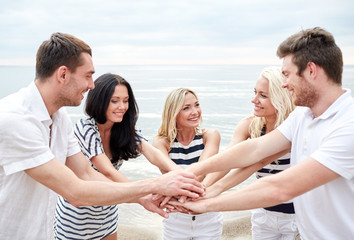 smiling friends putting hands on top of each other