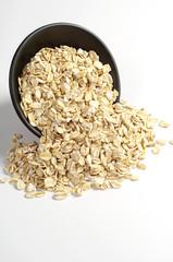 Oatmeal spilling on white background