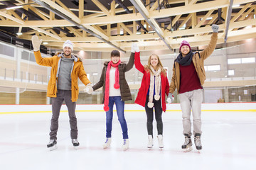 happy friends waving hands on skating rink