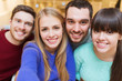group of smiling friends taking selfie