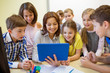 group of kids with teacher and tablet pc at school - 74507448
