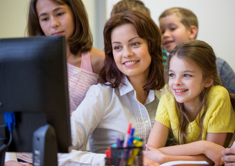 group of kids with teacher and computer at school