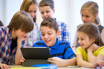 group of school kids with tablet pc in classroom