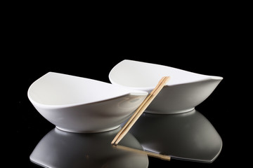 Two white ceramics bowls with bamboo chopsticks  on the glass ta