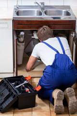 Repairman fixing the sink