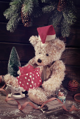 vintage teddy bear in santa hat holding christmas gift box