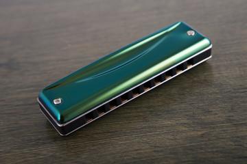 green harmonica on wooden board