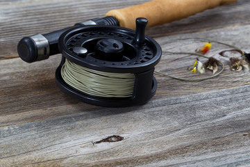 Close up of Fly Reel and Flies on Wood