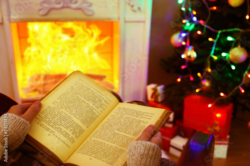 canvas print picture Woman holding book in front of fireplace