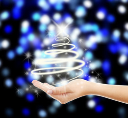 Christmas concept. Female hand with lights in shape of fir tree